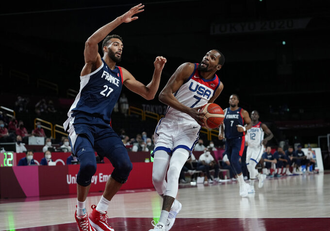 United States' Kevin Durant (7) drives around France's Rudy Gobert (27) during men's basketball gold medal game at the 2020 Summer Olympics, Saturday, Aug. 7, 2021, in Saitama, Japan. (AP Photo/Eric Gay)
