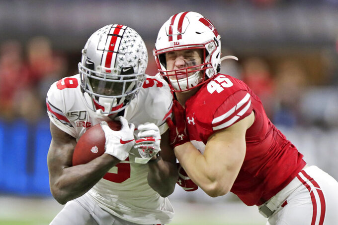 Ohio State wide receiver Binjimen Victor (9) is tackled by Wisconsin linebacker Leo Chenal (45) during the second half of the Big Ten championship NCAA college football game Saturday, Dec. 7, 2019, in Indianapolis. (AP Photo/Michael Conroy)