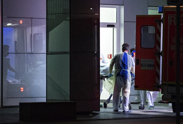 Medical staff in carry the first person infected with the coronavirus in the German state of North Rhine Westphalia out of an ambulance into the Liver and Infection Center of the University Hospital in Duesseldorf, Germany, Wednesday, Feb 26, 2020. (Guido Kirchner/dpa via AP)