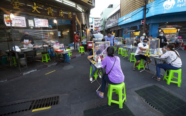 Customers eat street food behind plastic sheets to help curb the spread of the coronavirus in Bangkok, Thailand, Tuesday, May 12, 2020. Small restaurants are one of the few businesses that have been allowed to open during an easing of restrictions in Thailand's capital Bangkok imposed weeks ago to combat the spread of the coronavirus. (AP Photo/Sakchai Lalit)