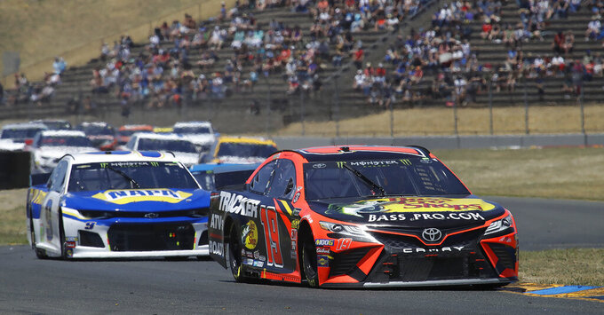 Martin Truex Jr., right, leads through a turn during a NASCAR Sprint Cup Series auto race Sunday, June 23, 2019, in Sonoma, Calif. (AP Photo/Ben Margot)