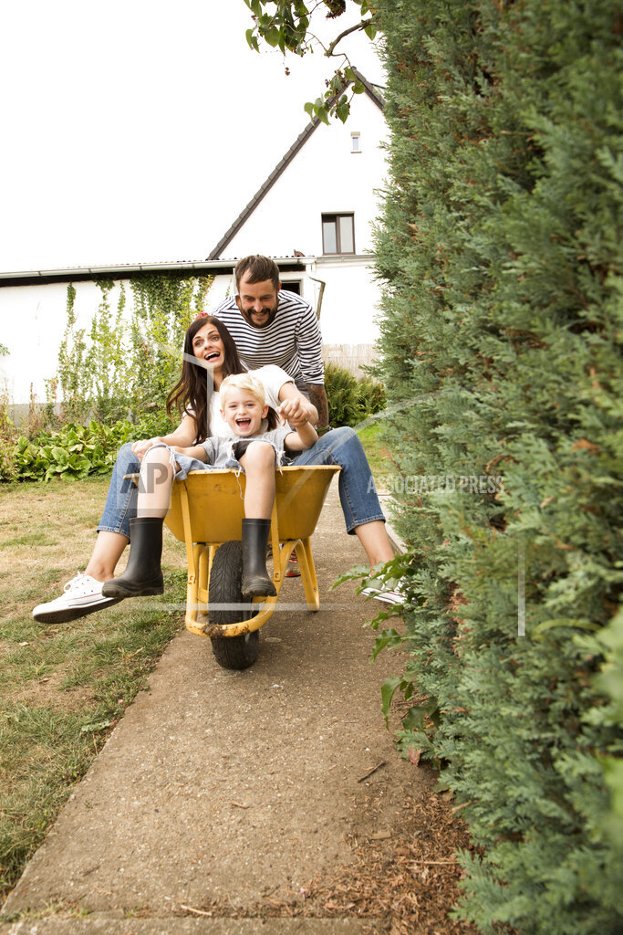Playful man pushing wife and son sitting in wheelbarrow in garden