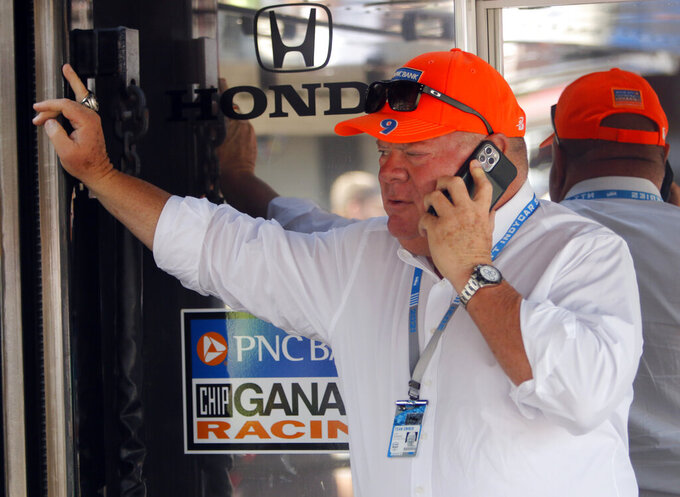 Car owner Chip Ganassi talks on his phone in the paddock before an IndyCar race at Mid-Ohio Sports Car Course in Lexington, Ohio, Sunday, July 4, 2021. (AP Photo/Tom E. Puskar)