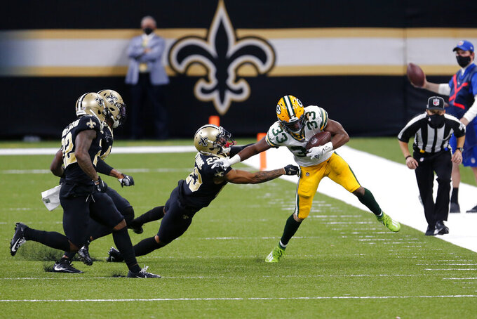 Green Bay Packers running back Aaron Jones (33) carries against New Orleans Saints cornerback Marshon Lattimore (23) in the first half of an NFL football game in New Orleans, Sunday, Sept. 27, 2020. (AP Photo/Brett Duke)