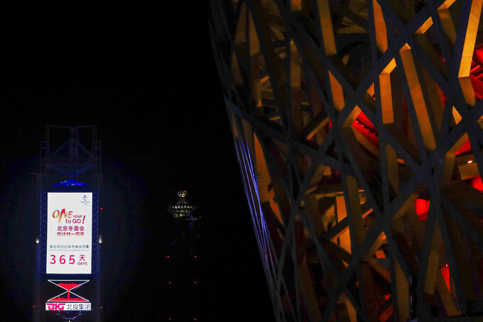 "A countdown clock showing one year to go for the 2022 Beijing Olympics stands near the Olympics Tower, far center, and National Stadium, also known as the Bird's Nest, which will again be a venue for the Olympics, in Beijing on Wednesday, Feb. 3, 2021. The 2022 Beijing Winter Olympics will open a year from now. Most of the venues have been completed as the Chinese capital becomes the first city to hold both the Winter and Summer Olympics. Beijing held the 2008 Summer Olympics. But these Olympics are presenting some major problems. They are already scarred by accusations of rights abuses including ""genocide""against more than 1 million Uighurs and other Muslim ethnic groups in western China. (AP Photo/Andy Wong)"