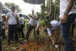 In this Jan. 29, 2020 photo, Howard Buffett plants cocoa plant at a farm in La Gabarra, Colombia. Buffett began working in Colombia in 2008, helping pop star Shakira set up schools in her hometown of Barranquilla. He's also funded an army unit removing thousands of landmines strewn across former conflict zones. (AP Photo/Ivan Valencia)