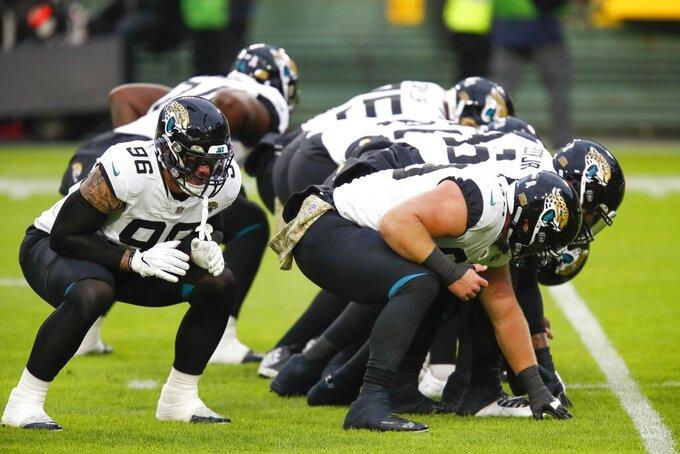 Jacksonville Jaguars players warm up before an NFL football game Sunday, Nov. 15, 2020, in Green Bay, Wis. (AP Photo/Matt Ludtke)