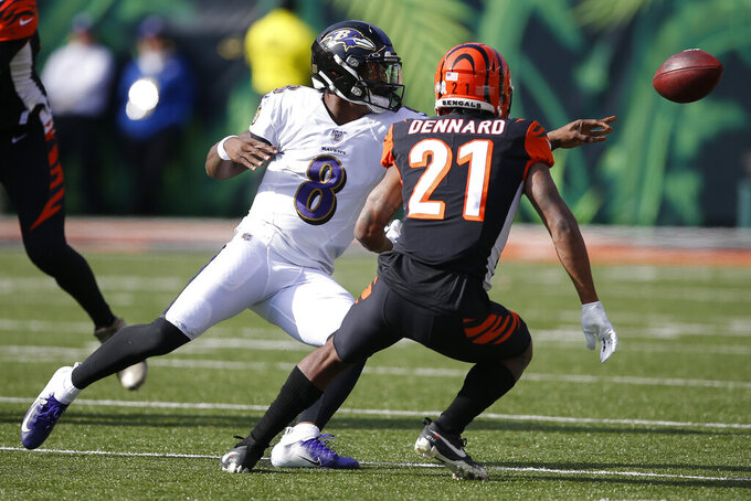 Baltimore Ravens quarterback Lamar Jackson (8) tosses the ball against Cincinnati Bengals defensive back Darqueze Dennard (21) during the first half of NFL football game, Sunday, Nov. 10, 2019, in Cincinnati. (AP Photo/Gary Landers)