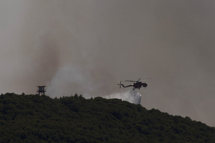 A firefighting helicopter drops water as fire burns outside the port town of Lavrio, some 60 kilometers (37 miles) south of the Athens, on Thursday, July 16, 2020. A children's summer camp and dozens of homes have been evacuated due to a wildfire south of Athens, where high winds hampered an effort to contain the blaze. (AP Photo/Petros Giannakouris)