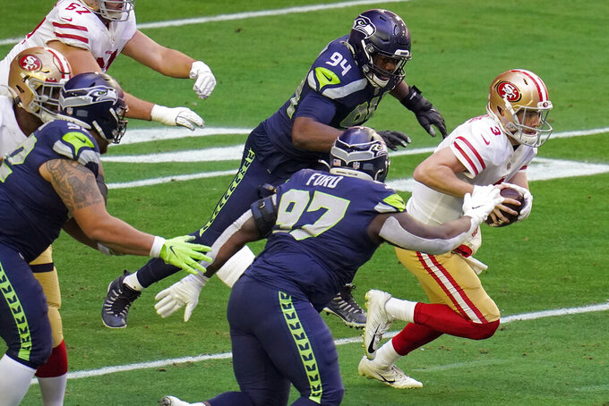 San Francisco 49ers quarterback C.J. Beathard (3) scrambles as Seattle Seahawks defensive end Rasheem Green (94) and defensive tackle Poona Ford (97) pursue during the first half of an NFL football game, Sunday, Jan. 3, 2021, in Glendale, Ariz. (AP Photo/Ross D. Franklin)