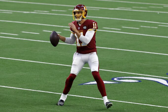 Washington Football Team quarterback Alex Smith (11) scrambles out of the pocket attempting to throw a a pass in the first half of an NFL football game against the Dallas Cowboys in Arlington, Texas, Thursday, Nov. 26, 2020. (AP Photo/Ron Jenkins)