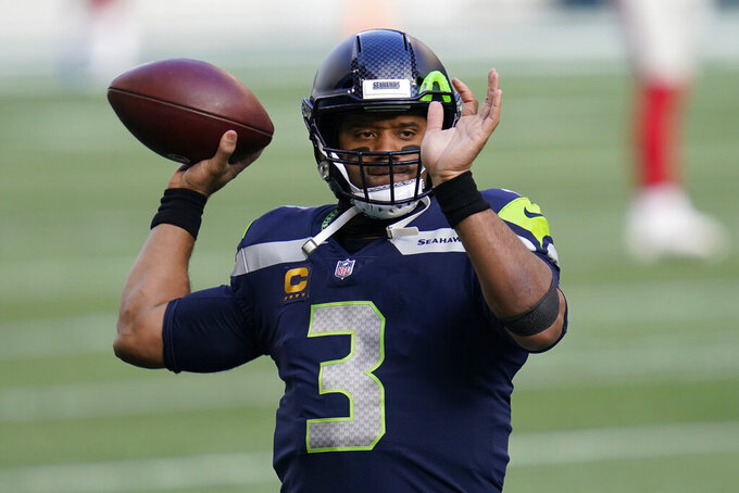 Seattle Seahawks quarterback Russell Wilson passes as he warms up for an NFL football game against the New York Giants, Sunday, Dec. 6, 2020, in Seattle. (AP Photo/Elaine Thompson)