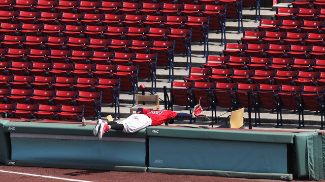 Boston Red Sox right fielder Alex Verdugo jokingly stretches for a foul ball by Rafael Devers in a seating area empty of fans during an intra-squad baseball game at Fenway Park on Thursday, July 9, 2020, in Boston. (AP Photo/Charles Krupa)