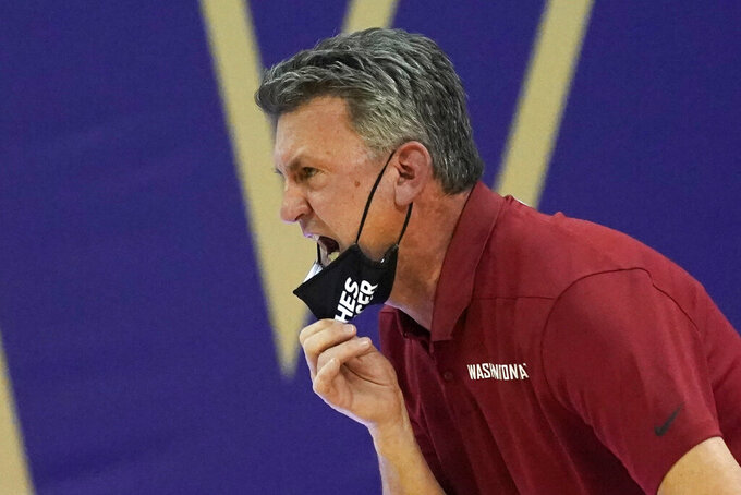 Washington State head coach Kyle Smith pulls down his mask to yell toward the court in the first half of an NCAA college basketball game against Washington, Sunday, Jan. 31, 2021, in Seattle. (AP Photo/Elaine Thompson)