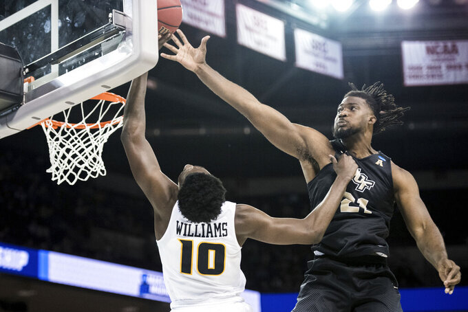 Central Florida forward Chad Brown (21) blocks a shot by VCU guard Vince Williams (10) during the second half of a first-round game in the NCAA men's college basketball tournament Friday, March 22, 2019, in Columbia, S.C. Central Florida won 73-58. (AP Photo/Sean Rayford)