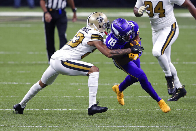 New Orleans Saints cornerback Marshon Lattimore tries to tackle Minnesota Vikings wide receiver Justin Jefferson (18) in the first half of an NFL football game in New Orleans, Friday, Dec. 25, 2020. (AP Photo/Butch Dill)