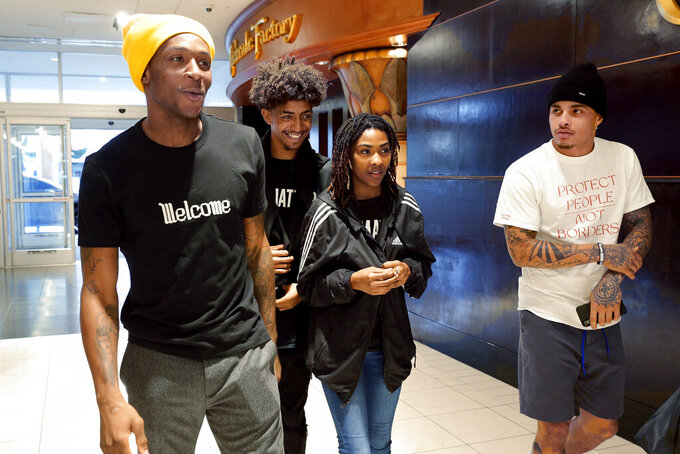 Houston Texans players De'Andre Hopkins, left, and Kenny Stills, right, shop for Christmas clothes with Jadon Cofield and Miracle Washington-Tribble, center right, Monday, Dec. 16, 2019, at Galleria Mall in Houston. The two teens are beneficiaries of Eight Million Stories, a Houston program which helps 14-18-year-olds who have either quit or been kicked out of school continue their education, find employment and receive emotional support. (AP Photo/Michael Wyke)