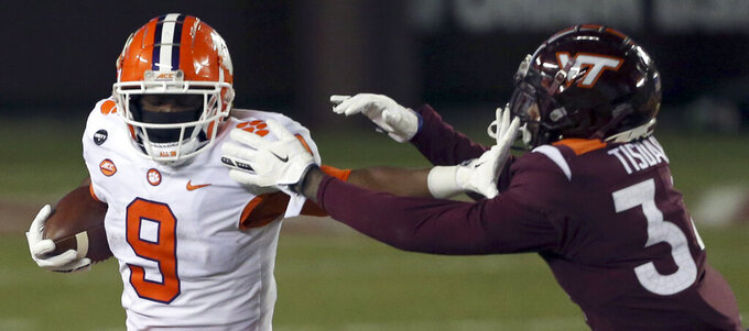 Clemson's Travis Etienne, left, escapes from Virginia Tech's Alan Tisdale during the second quarter of an NCAA college football game Saturday, Dec. 5, 2020, in Blacksburg, Va. (Matt Gentry/The Roanoke Times via AP, Pool)
