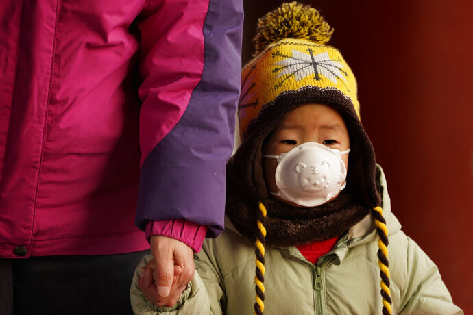 A child wears a mask with a tiger imprint as he visits Jingshan park during a snow day in Beijing Tuesday, Jan. 19, 2021. China is now dealing with coronavirus outbreaks across its frigid northeast, prompting additional lockdowns and travel bans. (AP Photo/Ng Han Guan)