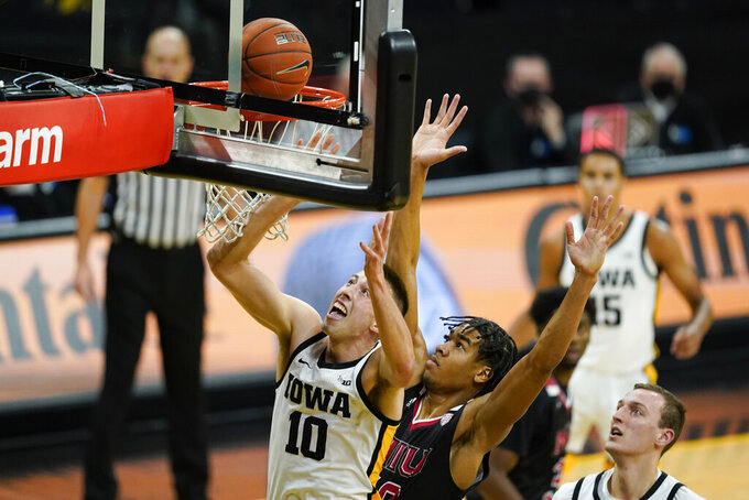 Iowa guard Joe Wieskamp (10) drives to the basket in front of Northern Illinois guard Anthony Crump during the first half of an NCAA college basketball game, Sunday, Dec. 13, 2020, in Iowa City, Iowa. (AP Photo/Charlie Neibergall)