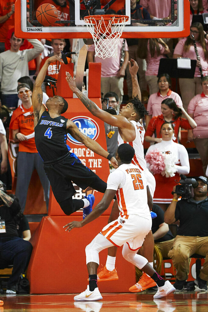 Buffalo guard Davonta Jordan (4) shoots over Bowling Green forward Demajeo Wiggins (1) and forward Daeqwon Plowden (25) in the second half of an NCAA college basketball game in Bowling Green, Ohio, Friday, Feb. 1, 2019. (AP Photo/Rick Osentoski)