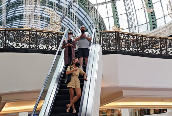 People visit the Mall of the Emirates in Dubai, United Arab Emirates, Thursday, April 15, 2021. The Middle East's largest operator of malls, Majid Al Futtaim, expects revenue and earnings to climb back to pre-pandemic levels by the end of next year and is moving full steam ahead with plans to develop its biggest mall ever. (AP Photo/Kamran Jebreili)