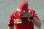 Ferrari driver Sebastian Vettel of Germany touches his face as he walks in the pit lane prior to the Italian Formula One Grand Prix, at the Monza racetrack in Monza, Italy, Sunday Sept. 6, 2020. (AP Photo/Luca Bruno, Pool)