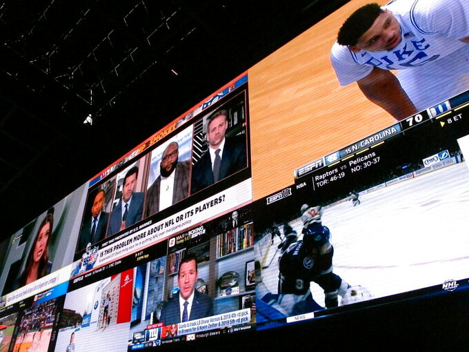 This March 8, 2019 photo shows giants video screens inside the sports betting lounge at the Tropicana casino in Atlantic City N.J. Figures released on March 13, 2019 show New Jersey gamblers have wagered almost $2 billion on sporting events since it started nine months ago. (AP Photo/Wayne Parry)