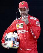 Ferrari driver Sebastian Vettel of Germany removes his glasses as he poses for a photo ahead of the Australian Grand Prix in Melbourne, Australia, Thursday, March 14, 2019. (AP Photo/Rick Rycroft)