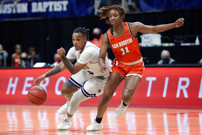 Stephen F. Austin guard Zya Nugent (22) drives around Sam Houston State forward Courtney Cleveland (11) during the second half of an NCAA college basketball game for the Southland Conference women's tournament championship Sunday, March 14, 2021, in Katy, Texas. (AP Photo/Michael Wyke)