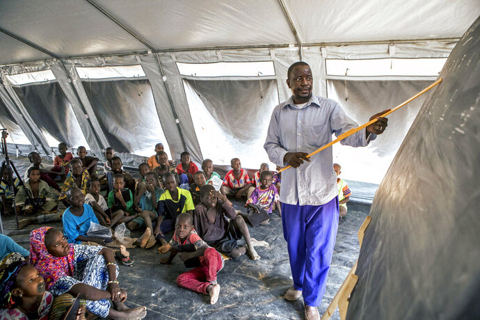 In this photo provided by UNICEF and taken on April 24, 2019, Boureima Tall, a displaced teacher at the temporary learning space teaches numbers in front of his class in Socoura, Mali. Before the crisis, Boureima worked in the town of Bankass as a teacher. More than 9,000 schools have closed and more than 1.9 million children in West and Central Africa have been forced out of school because of increasing violence in the region and attacks specifically targeting education facilities, UNICEF said Friday, Aug, 23. Attacks on schools in Mali, Burkina Faso and Niger, where an Islamic extremist insurgency has grown, have doubled in the past two years, the agency said. (Dicko/UNICEF via AP)