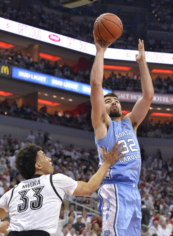 North Carolina forward Luke Maye (32) attempts a shot over the defense of Louisville forward Jordan Nwora (33) during the first half of an NCAA college basketball game in Louisville, Ky., Saturday, Feb. 2, 2019. (AP Photo/Timothy D. Easley)