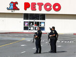 Police stand watch at the scene of a shooting at the Tanforan Mall in San Bruno, Calif., Tuesday, July 2, 2019. Police are searching for suspects after at least two people were wounded in a mall shooting near San Francisco on Tuesday that led to region-wide transit delays at rush hour. (AP Photo/Stephanie Mullen)