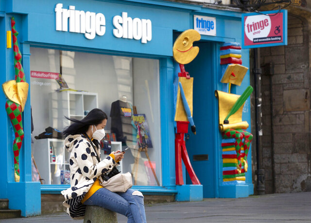A woman scans her smartphone outside the Fringe Shop on the Royal Mile in Edinburgh, Scotland Friday Aug. 21, 2020.  One of the biggest casualties of the coronavirus has been the Edinburgh Fringe Festival, a sprawling theatre and comedy arts and street festival that last year sold more than 3 million tickets, but this year's events are canceled, leaving artists adrift and many businesses struggling to make a living without the usual throng of tourists. (AP Photo/David Cheskin)