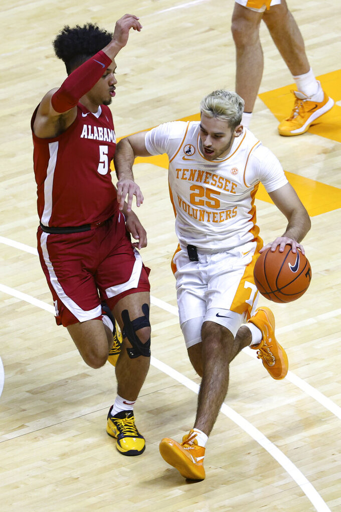 Tennessee guard Santiago Vescovi (25) moves the ball against Alabama's Jaden Shackelford (5) during an NCAA college basketball game Saturday, Jan. 2, 2021, in Knoxville, Tenn. (AP Photo/Randy Sartin, Pool)