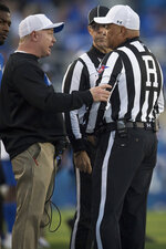 Kentucky head coach Mark Stoops talks with officials during the second half an NCAA college football game against Georgia in Lexington, Ky., Saturday, Nov. 3, 2018. (AP Photo/Bryan Woolston)