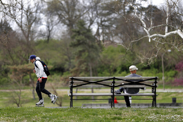 People relax and exercise in Forest Park Friday, April 3, 2020, in St. Louis. The city is under a stay-at-home order asking everyone to stay inside and away from others as much as possible, with some exceptions such as going out for groceries or exercise, in an effort to slow the spread of the coronavirus. (AP Photo/Jeff Roberson)