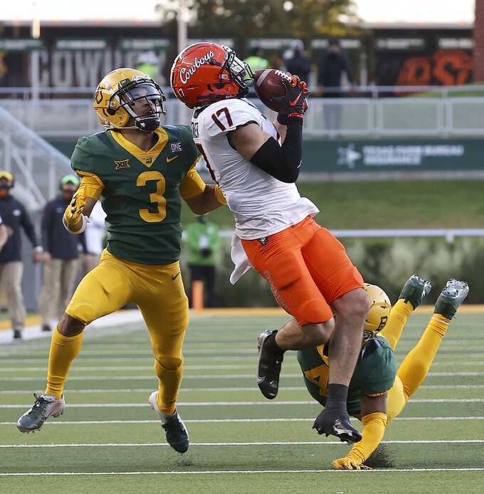 Oklahoma State wide receiver Dillon Stoner (17) catches a pass against Baylor cornerback Raleigh Texada (3) in the second half of an NCAA college football game, Saturday, Dec. 12, 2020, in Waco, Texas. (Jerry Larson/Waco Tribune-Herald via AP)