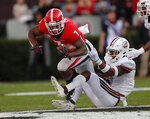 Georgia running back D'Andre Swift (7) tries to break free from Massachusetts safety Brice McAllister (2) during the first half of an NCAA college football game Saturday, Nov. 17, 2018, in Athens, Ga. (AP Photo/John Bazemore)