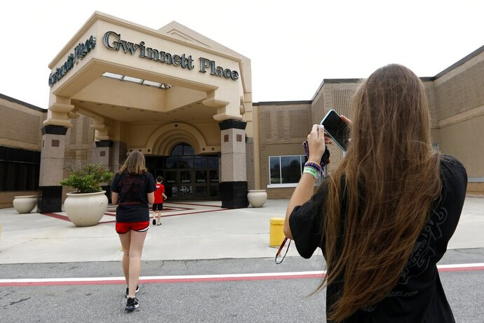 FILE - In this July 23, 2019 file photo, Brinley Rawson, a 17-year-old Stranger Things fan from Gwinnett County, snaps a photo of Gwinnett Place Mall in Duluth, Ga.  The Georgia mall heavily featured in the latest season of Netflix's