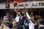 Kansas State forward Antonio Gordon (11) shoots in front of Oklahoma State forward Kalib Boone, right, in the first half of an NCAA college basketball game Saturday, Feb. 13, 2021, in Stillwater, Okla. (AP Photo/Sue Ogrocki)