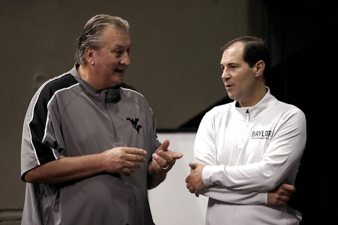 Baylor coach Scott Drew, right, and West Virginia coach Bob Huggins talk during Big 12 NCAA college basketball media day Wednesday, Oct. 20, 2021, in Kansas City, Mo. (AP Photo/Charlie Riedel)