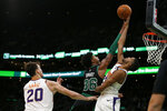 Phoenix Suns forward Mikal Bridges (25) blocks a shot by Boston Celtics guard Marcus Smart (36) as Suns forward Dario Saric (20) looks on during the second half of an NBA basketball game, Saturday, Jan. 18, 2020, in Boston. (AP Photo/Mary Schwalm)