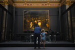 A limited amount of visitors admire Rembrandt's Night Watch, rear, at the reopened Rijksmuseum in Amsterdam, Netherlands, Monday, June 1, 2020. The Dutch government took a major step to relax the coronavirus lockdown, with bars, restaurants, cinemas and museums reopening under strict conditions. (AP Photo/Peter Dejong)