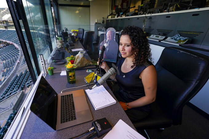 Amelia Schimmel, the new public address announcer for the Oakland Athletics, sits in the press box before a baseball game against the Houston Astros, Thursday, April 1, 2021, on opening day in Oakland, Calif. Schimmel succeeds the late Dick Callahan, who passed away in January after serving as the team's PA announcer for 15 seasons. (AP Photo/Tony Avelar)