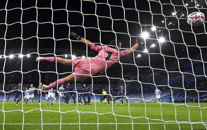 FC Porto goalkeeper Agustin Marchesin dives in vain as Manchester City's Ilkay Gundogan scores his side's second goal during the Champions League group C soccer match between Manchester City and FC Porto at the Etihad stadium in Manchester, England, Wednesday, Oct. 21, 2020. (Paul Ellis/PA via AP)