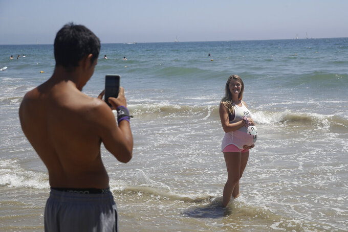 Visitors take photos on the beach Sunday, July 12, 2020, in Santa Monica, Calif., amid the coronavirus pandemic.  A heat wave has brought crowds to California's beaches as the state grappled with a spike in coronavirus infections and hospitalizations. (AP Photo/Marcio Jose Sanchez)