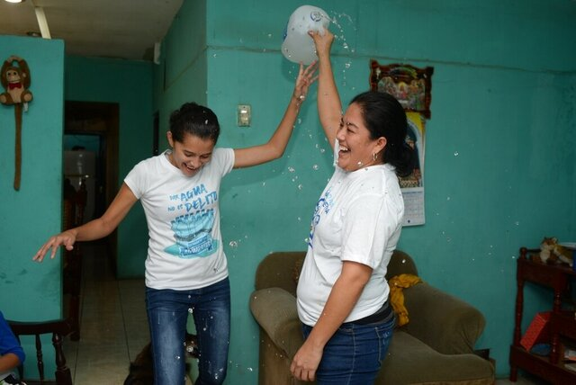 Ivania Alvarez holds up an open jug of water to celebrates with Neyma Hernandez after their release from prison, at her home in Managua, Nicaragua, Monday, Dec. 30, 2019. The two belonged to the