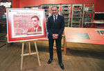"""Governor of the Bank of England, Mark Carney poses for a photo with the artwork for the concept of the new 50 pound notes, after announcing that Second World War code-breaker Alan Turing has been selected to feature on the new notes, at the Science and Industry Museum, in Manchester, England, Monday July 15, 2019.  The Bank of England has chosen codebreaker and computing pioneer Alan Turing as the face of the country's new 50 pound note. Governor Mark Carney said Monday that Turing was """"a giant on whose shoulders so many now stand."""" Turing's work cracking Nazi Germany's secret communications helped win World War II, but after the war he was prosecuted for homosexuality, and died in 1954 after eating an apple laced with cyanide. (Peter Byrne/PA via AP)"""
