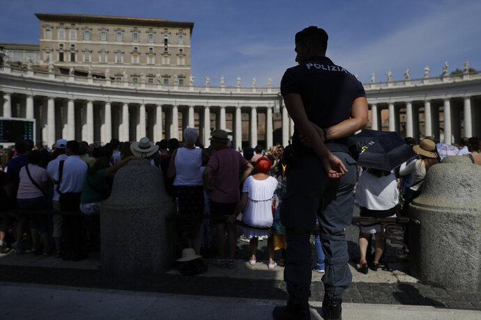 An Italian Police officer watch over faithful as he patrols in St. Peter's Square during Pope Francis' Angelus noon prayer at the Vatican, Sunday, Sept. 15, 2019. (AP Photo/Gregorio Borgia)